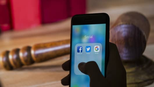 A smart phone with the icons for the Facebook, Twitter, Google apps.
