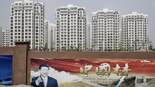 A poster featuring Xi Jinping, China's president, hangs on a wall as residential and commercial buildings stand in the background in China's Hebei province.