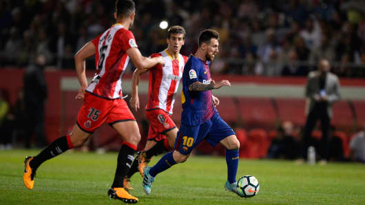 Girona's defender Juanpe Ramirez (L) vies with Barcelona's forward from Argentina Lionel Messi during the Spanish league football match Girona FC vs FC Barcelona at the Montilivi stadium in Girona on September 23, 2017.