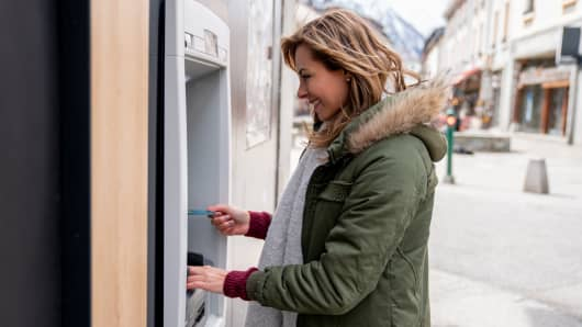 Happy woman making a cash withdrawal at an ATM