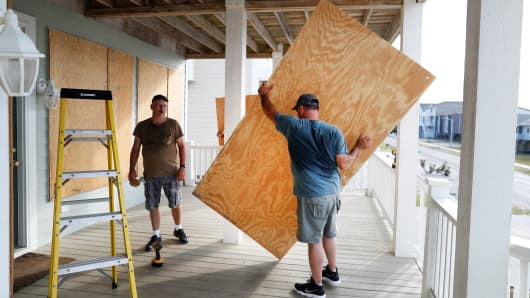 Workers prepare a house with storm shutters ahead of the arrival of Hurricane Florence in Ocean Isle Beach, North Carolina, September 12, 2018.