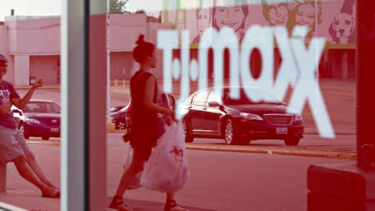 The reflection of shoppers are seen in a window at a TJ Maxx store in Peoria, Illinois.