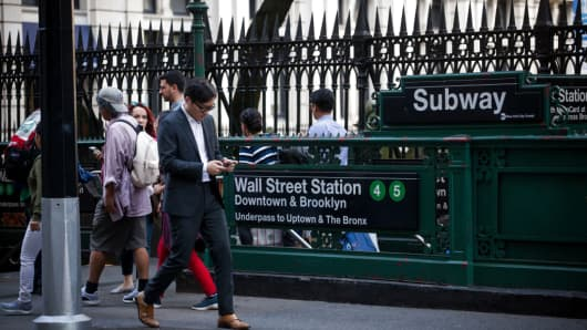 A pedestrian views a mobile device while walking past the Wall Street subway station near the New York Stock Exchange (NYSE) in New York.