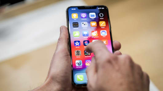An attendee demonstrates the Apple  iPhone XR smartphone during an event at the Steve Jobs Theater in Cupertino, California, on Wednesday, Sept. 12, 2018.