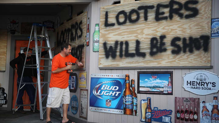 Doug Lewis (L) and Chris Williams use plywood with the words 'Looters will be shot' to cover the windows of Knuckleheads bar as they try to protect the business ahead of the arrival of Hurricane Florence on September 12, 2018 in Myrtle Beach, United States. Hurricane Florence is expected on Friday possibly as a category 4 storm along the Virginia, North Carolina and South Carolina coastline.