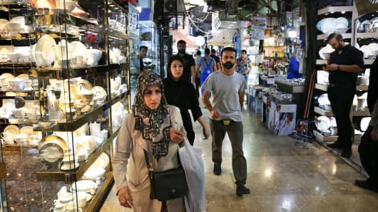 In this Thursday, Sept. 6, 2018, photo, people walk through the Grand Bazaar where Chinese-made goods have flooded the market, in Tehran, Iran.