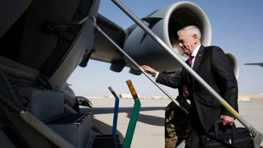 Secretary James Mattis climbs up the steps as he boards a US Air Force C-17.