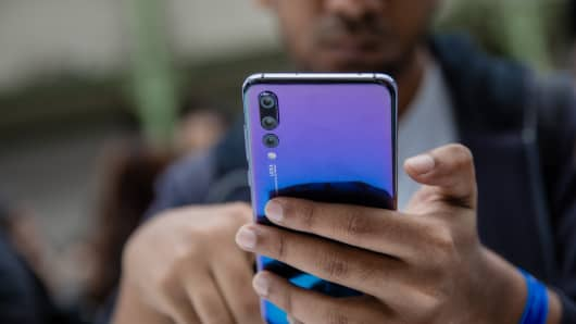 An attendee inspects a P20 Pro smartphone, manufactured by Huawei Technologies Co., during its unveiling in Paris, France, on Tuesday, March 21, 2018.