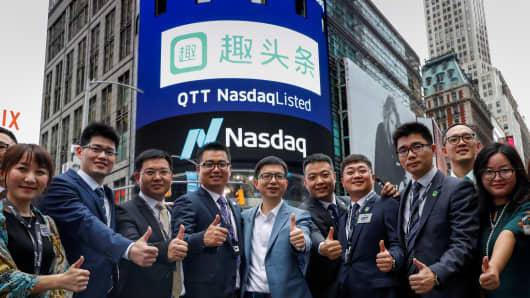 Eric Siliang Tan, (C) Chairman and CEO of Qutoutiao Inc., poses with company officials during the company's IPO at the Nasdaq MarketSite in New York City, U.S., September 14, 2018.