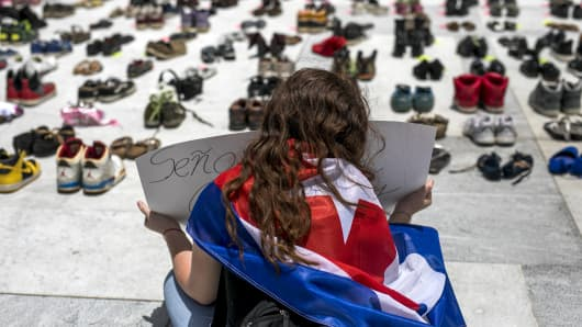 A demonstrator holds a sign near empty pairs of shoes displayed outside the Capitol building during a protest against the government's reporting of the death toll from  Hurricane Maria in San Juan, Puerto Rico, on Friday, June 1, 2018. Hurricane Maria probably killed about 5,000 people in Puerto Rico last year even though the official count remains at just 64, according to a Harvard University study released Tuesday.