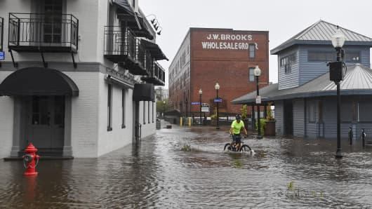 A bicyclist rides through a flooded South Water Street as Hurricane Florence makes landfall on September 14, 2018 in Wilmington, NC.