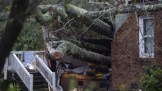 A tree that fell on a house, killing two people, is seen during Hurricane Florence in Wilmington, North Carolina on September 14, 2018. - A mother and her infant were killed when a tree fell on their house in Wilmington, North Carolina, the first reported fatalities from Hurricane Florence, police said Friday. Wilmington police tweeted that the father was transported to the hospital with unspecified injuries.