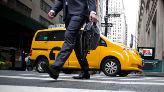 A man walks along Wall Street as a taxi turns a corner near the New York Stock Exchange in New York, on Monday, June 11, 2018.