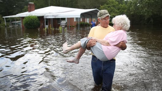Bob Richling carries Iris Darden as water from the Little River starts to seep into her home on September 17, 2018 in Spring Lake, North Carolina.