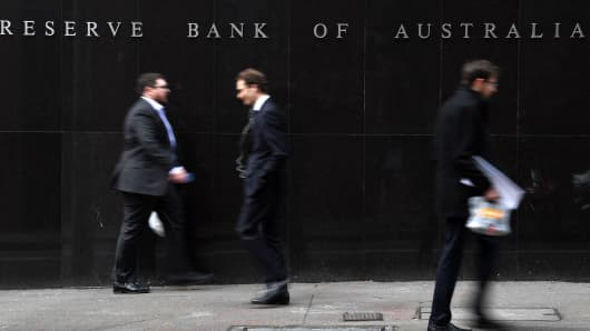 Office employees walk in front of the Reserve Bank of Australia in Sydney on September 4, 2018.