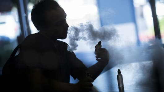 A customer holds a bottle of flavored vape juice while exhaling vapor from an electronic cigarette at the NXNW Vapor store in Sacramento, California.