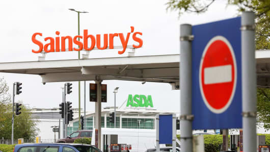 A sign from Sainsbury stands on Monday, April 30, 2018, on a gas station portal overlooking an Asda sign above the entrance of the supermarket in Watford, UK.