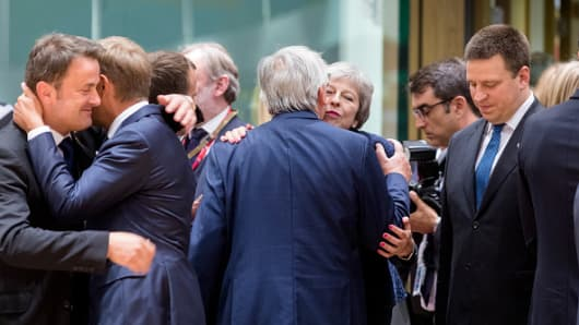 Tthe President of the European Commission Jean-Claude Juncker embraces the Prime Minister of the United Kingdom Theresa May on June 28, 2018 in Brussels, Belgium.