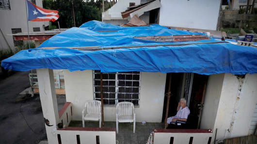 Lucila Cabrera, 86, sits at the porch of her house covered by plastic tarps over a damaged roof by Hurricane Maria, a year after the storm devastated Puerto Rico, near Barceloneta, Puerto Rico, September 18, 2018.