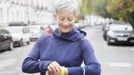 Female senior runner checks activity tracker.