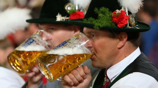 Visitors of the Oktoberfest beer festival drink a mug of beer in Munich, Germany.