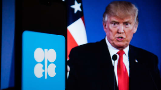 OPEC (Organization of Petroleum Exporting Countries) logo is seen on a mobile phone with the President of United States of America, Donald Trump on the background.