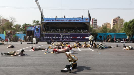 Injured soldiers lie on the ground at the scene of an attack on a military parade that was marking the anniversary of the outbreak of its devastating 1980-1988 war with Saddam Hussein's Iraq, Ahvaz, Khuzestan, September 22.