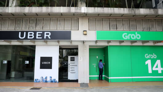 Signage for Uber Technologies and Grab are displayed outside a building in Singapore, on April 26, 2018.
