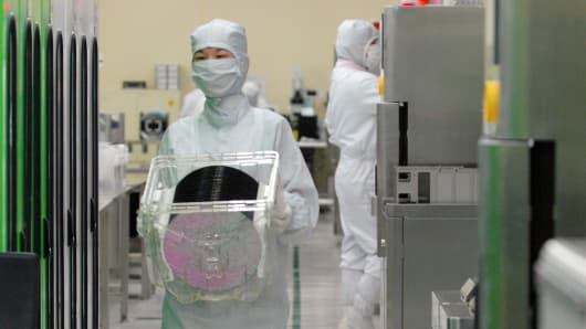 An employee carries a box containing silicon wafers at the production line of Hana Micron Inc.'s plant in Asan, South Korea.