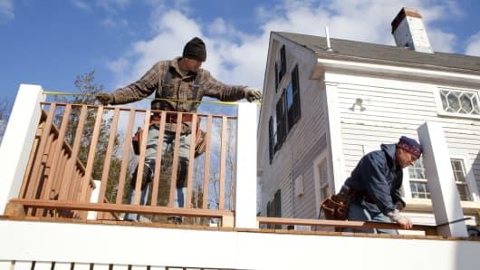 Carpenters  build a new deck on the back of an 1840's home they're renovating in Cohasset, Massachusetts.