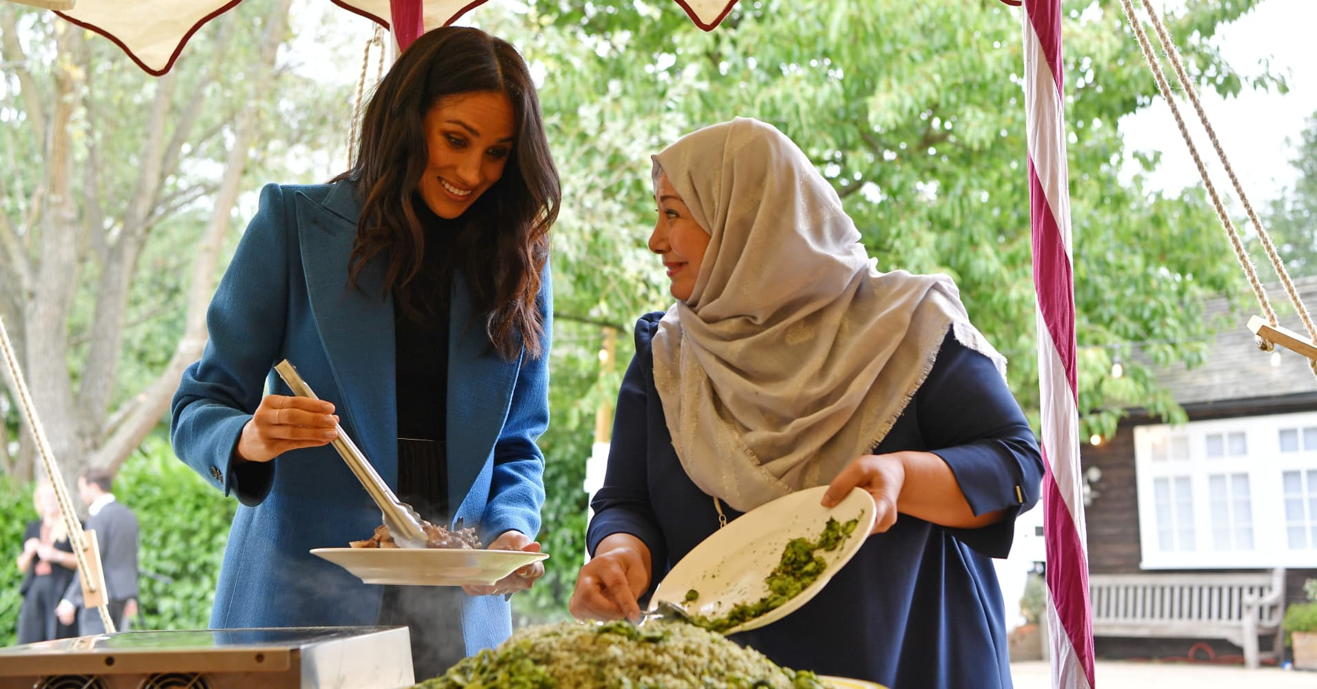Meghan, Duchess of Sussex helps to prepare food at an event to mark the launch of a cookbook with recipes from a group of women affected by the Grenfell Tower fire at Kensington Palace on Sept. 20.