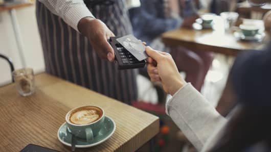 Customer with credit card paying worker with contactless payment in cafe