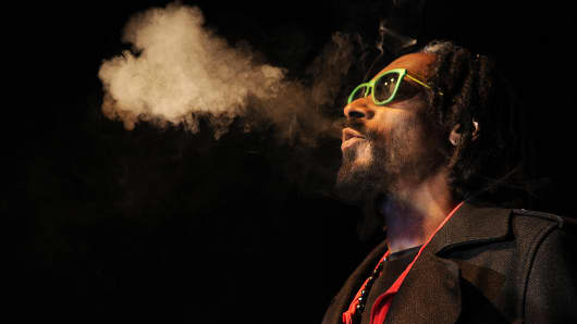 Snoop Dogg exhales a heart-shaped cloud of marijuana smoke while doing a Q&A with the audience after the screening of his documentary Reincarnated during the first-ever 'Green Carpet' event at the High Times US Cannabis Cup, April 19, 2013, Denver. (Photo by Seth McConnell/The Denver Post via Getty Images)