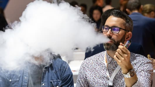 A man smokes an e-cigarrette and blows out the smoke at his stand at the InterTabac trade fair.