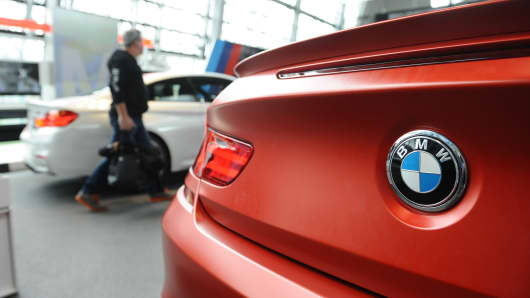 A visitor of BMW World walks past a BMW car during the annual accounts press conference of German car manufacturer BMW at the BWM World in Munich, Germany.