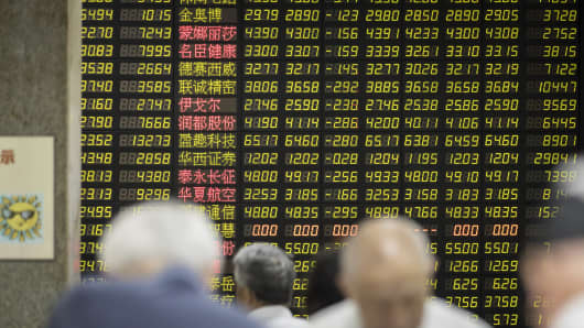 Investors stand in front of an electronic stock board at a securities brokerage in Shanghai, China, on May 30, 2018.