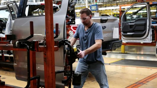 A Ford Motor assembly worker prepares to attach a door to a 2018 F150 pick-up truck at Ford's Dearborn Truck Plant in Dearborn, Michigan, September 27, 2018.