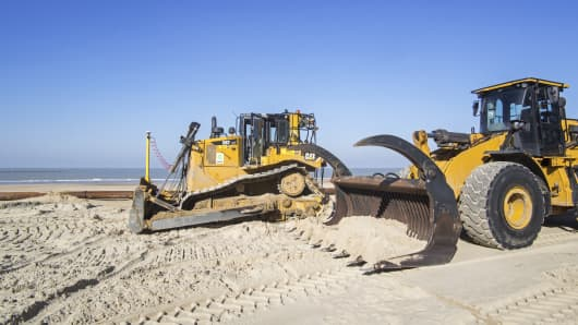 Bulldozers used for sand replenishment / beach nourishment to make wider beaches to reduce storm damage to coastal structures along the Belgian coast.