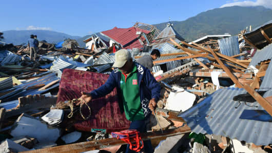 Indonesian men search forfamily members at their damaged house in the Balaroa village of Palu, Indonesia's Central Sulawesi on October 1, 2018.