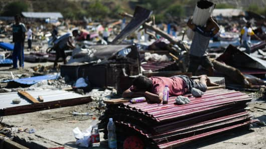 A man lays on a pile of tins as others salvage useable items from debris of collapsed buildings in Palu, Indonesia's Central Sulawesi on October 1, 2018, after an earthquake and tsunami hit the area on September 28.