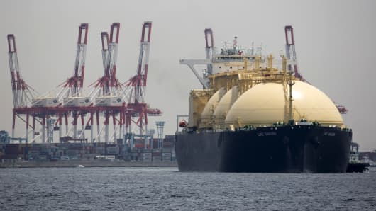 A liquefied natural gas tanker sails past a container terminal as it arrives in Yokohama, Japan, May 21, 2018.