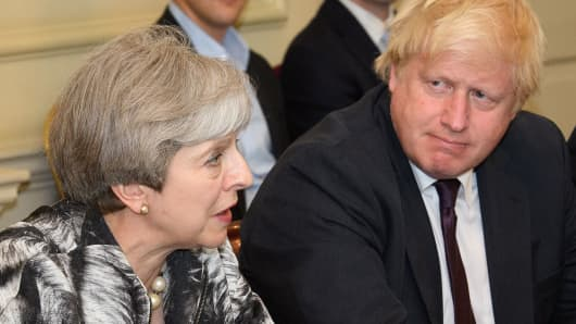 Britain's Prime Minister Theresa May (L) sits with Britain's Former Foreign Secretary Boris Johnson.