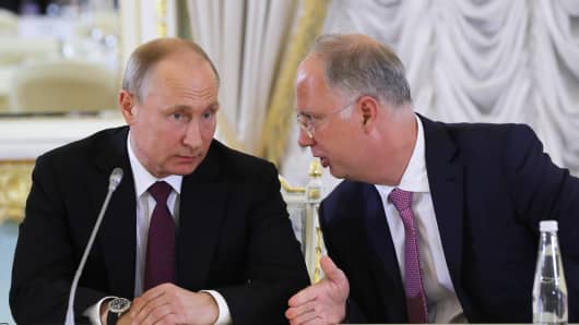 Russia's President Vladimir Putin (L) and Russian Direct Investment Fund CEO Kirill Dmitriev during a meeting with Russian Direct Investment Fund experts and representatives of international investment community at Konstantin Palace.