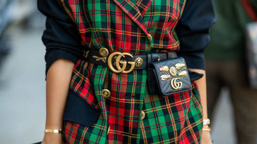 A woman wearing a Gucci belt and bag is seen during Paris Fashion Week in September 2018