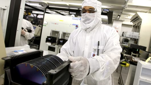 Robert Neely prepares to load a silicon wafer machine in a clean room at the Texas Instruments semiconductor fabrication plant in Dallas, Texas, U.S., on Tuesday, June 16, 2009. Texas Instruments Inc., the second-largest U.S. semiconductor maker, reported sales and profit that beat analysts' estimates on stronger demand for chips used in mobile phones and communications networks in China.  (Photo by Jason Janik/Bloomberg via Getty Images)