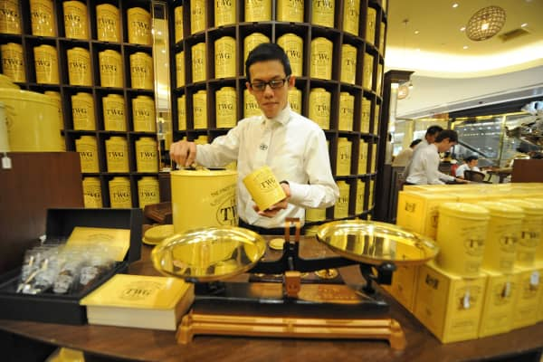 An employee of the TWG Tea company preparing tea for customer to take away at the counter in Singapore.