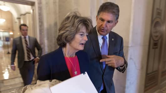 Sen. Lisa Murkowski (R-AK) (L) talks with Sen. Joe Manchin (D-WV) as they walk through the U.S. Capitol in Washington, DC.