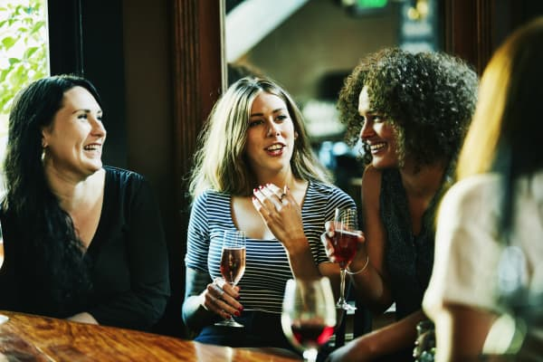 Laughing group of female friends in discussion in bar