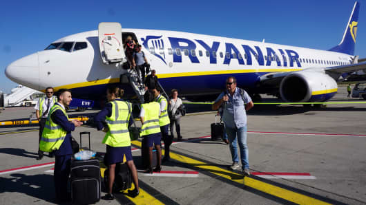 A Ryanair cabin crew awaits as passengers disembark on the tarmac at Brussels South Charleroi Airport in Charleroi on September 27, 2018.