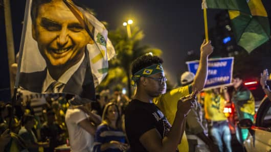 Supporters of Jair Bolsonaro, presidential candidate for the Social Liberal Party (PSL), celebrate after polls closed during the first round of presidential elections in Rio de Janeiro, Brazil, on Sunday, Oct. 7, 2018. Bolsonaro shot into the lead in Brazil's presidential vote in one of the most divisive elections in the country's history, the first official results showed. Photographer: Dado Galdieri/Bloomberg via Getty Images